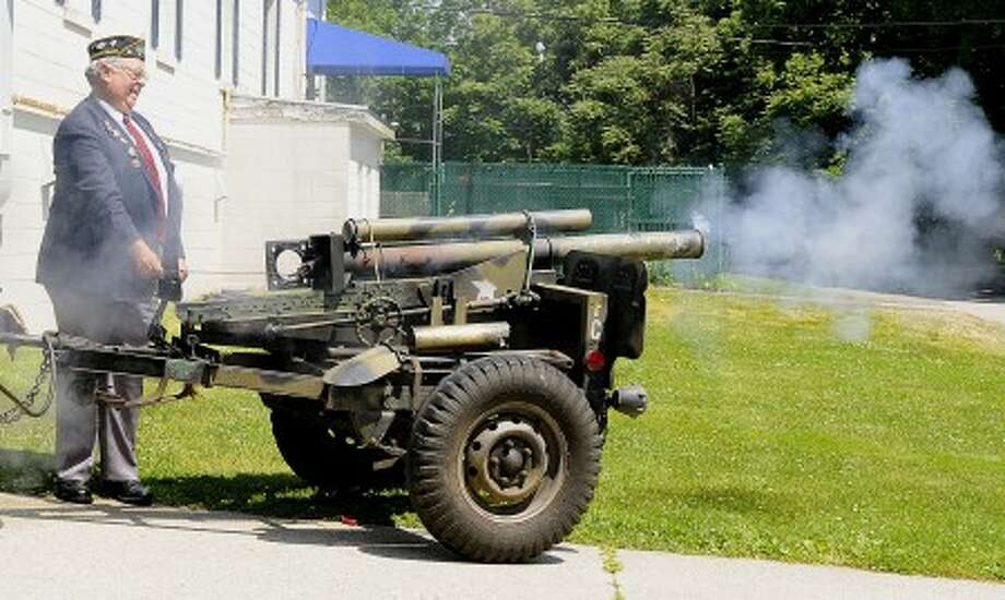"Richard Olson, commander of Norwalk''s American Legion Post 12, fires the first of three cannon shots Sunday during a ceremony honoring John ""Jack"" Campbell Jr. for his service in the Army during the Korean War."
