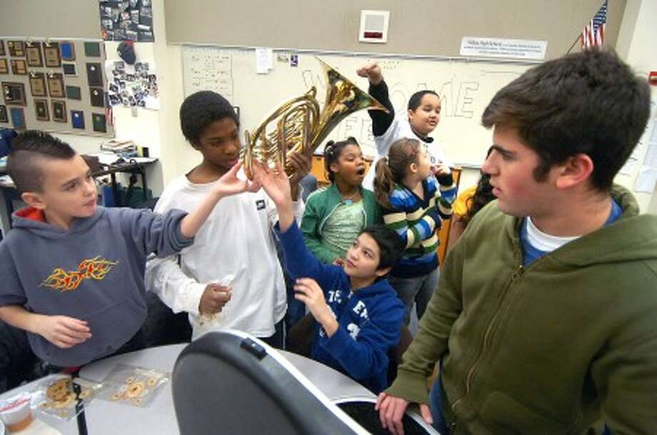 Photo/Alex von Kleydorff. Wilton High school Senior and Band Director Jason Herman shows a French Horn that was donated, to kids from Edison Elementary School in Bridgeport