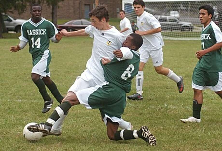 Trinity Catholic''s Sean Haas battles Wilson Lamitie of Bassick during the game in Bridgeport Tuesday. Hour photo / Erik Trautmann