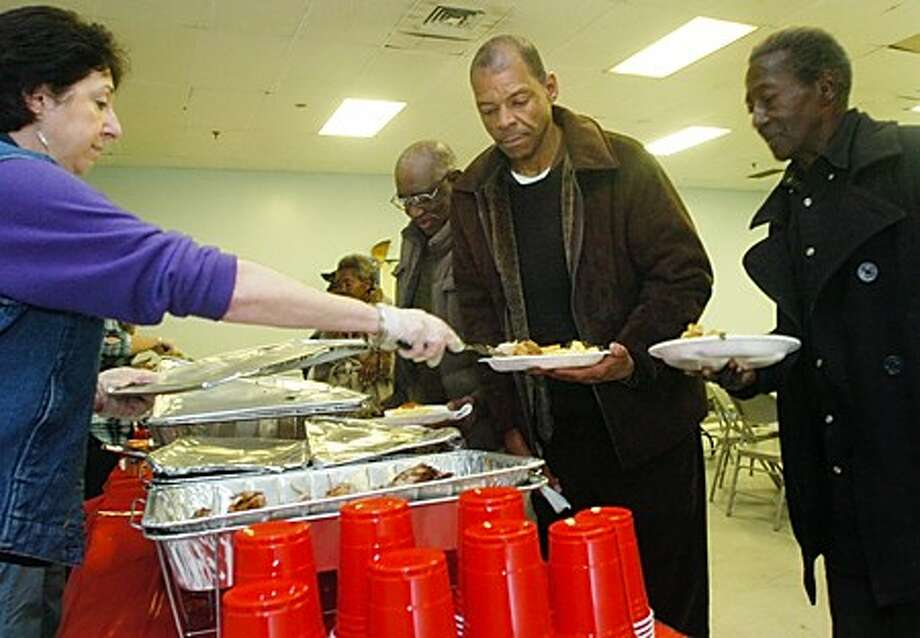 Derek Williams and John Wright get served a turkey dinner by volunteer Linda Lyons during a community dinner Thanksgiving Day at NEON. Hour photo / Erik Trautmann