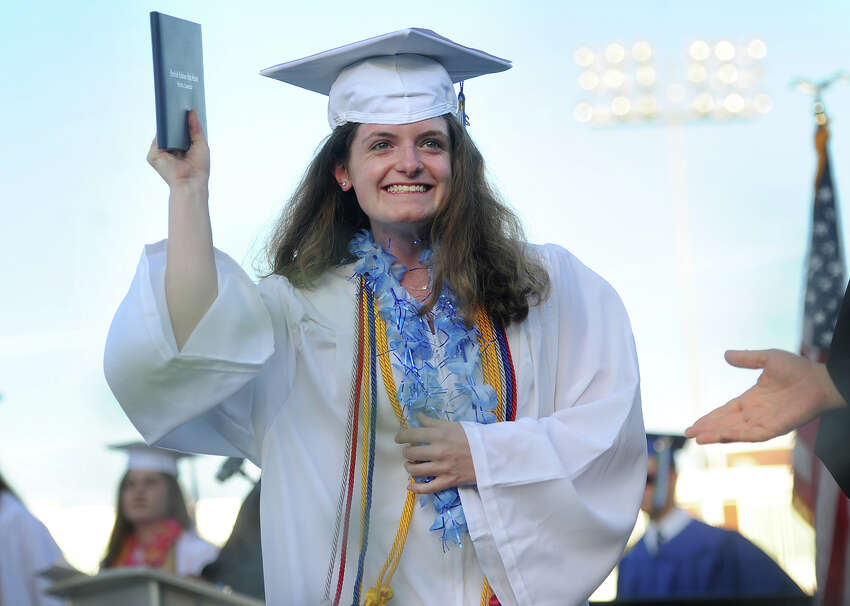 Graduate Wilhelmina Stuhlman shows her diploma to her family as she crosses the stage during the Fairfield Ludlowe High School graduation in Fairfield, Conn. on Thursday, June 16, 2016.