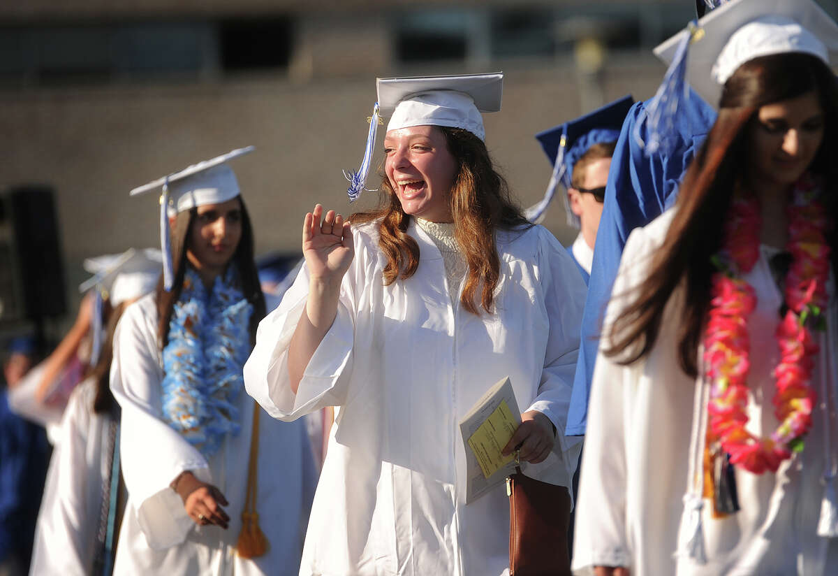 Graduate Angela Fortuna-Hodges waves to her family as she marches in to the Fairfield Ludlowe High School graduation in Fairfield, Conn. on Thursday, June 16, 2016.