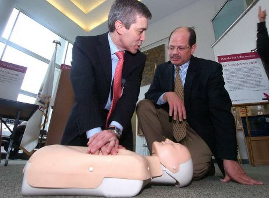 Photo/Alex von Kleydorff. l-r Stamford Hospital Cardiologist Dr. Tom Nero shows proper hands only CPR to Don Duboulay during a Hands for Life program at the Stamford Government Center.