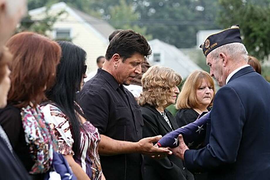 Frank Santo looks at the flag honoring his father, Franklin J. Santo, as he hands it over to American Legion Post 12 in Norwalk to be raised during their veteran of the month ceremony Sunday morning. Hour Photo / Danielle Robinson