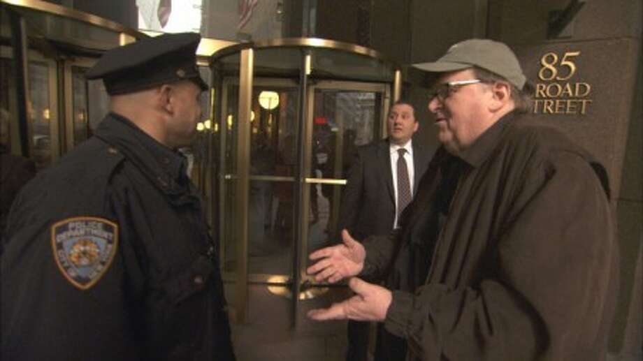 "In this film publicity image released by Overture Films, filmmaker Michael Moore talks to a police officer outside of Goldman Sachs headquarters in Manhattan in a scene from the documentary, ""Capitalism: A Love Story."" (AP Photo/Overture Films)"