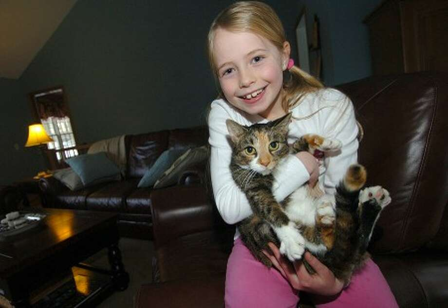 Photo/Alex von Kleydorff. 9yr old Shelby Connor hugs her adopted Calico cat ''Hazelnut''.