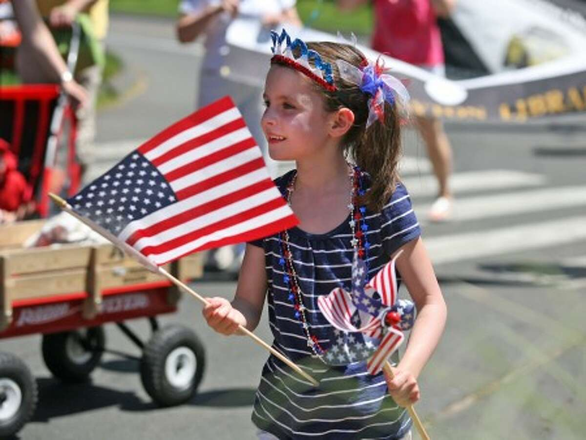 Katherine Klien, 7, waves a flag as she marches in Rowayton''''s annual Memorial Day Parade Sunday afternoon. Hour Photo / Danielle Robinson