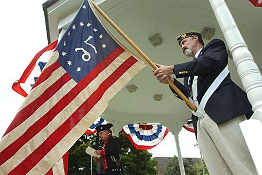 Roger Smith of the Sons of the American Revolution reads the Declaration of Independence and Harding Dies of the American Legion holds the Revolutionary Flag during an Independence day celebration of the Town Green Saturday. Hour photo / Erik Trautmann