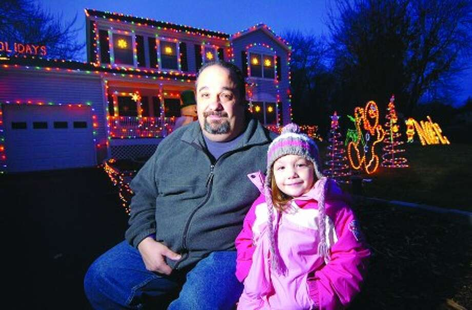Photo/Alex von Kleydorff. Mike Lockwood and 5yr old Kylie in front of their decorated house in Stamford.