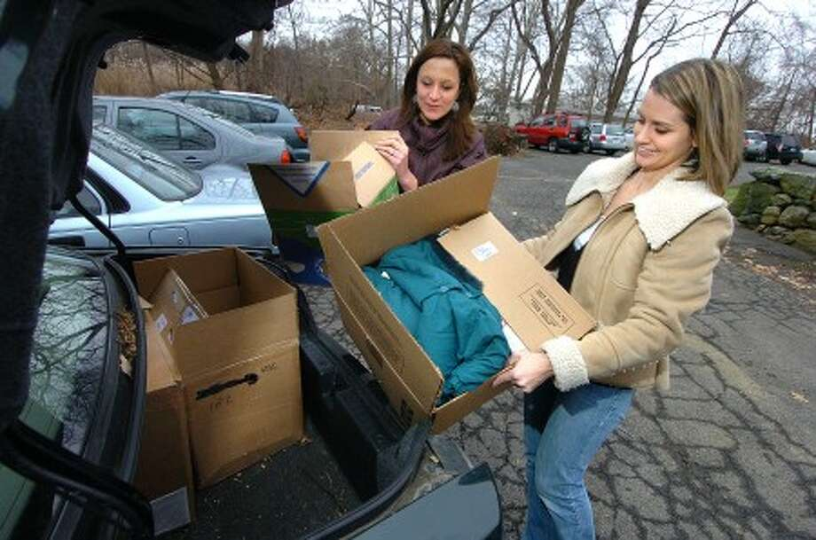 Photo/Alex von Kleydorff. Jessica Connoly, a volunteer with the Family Center Youth Parents Program unloads boxes of donated clothing at the Family Center in Stamford with help from Meg Robustelli, owner of Fairfield County Child.com .