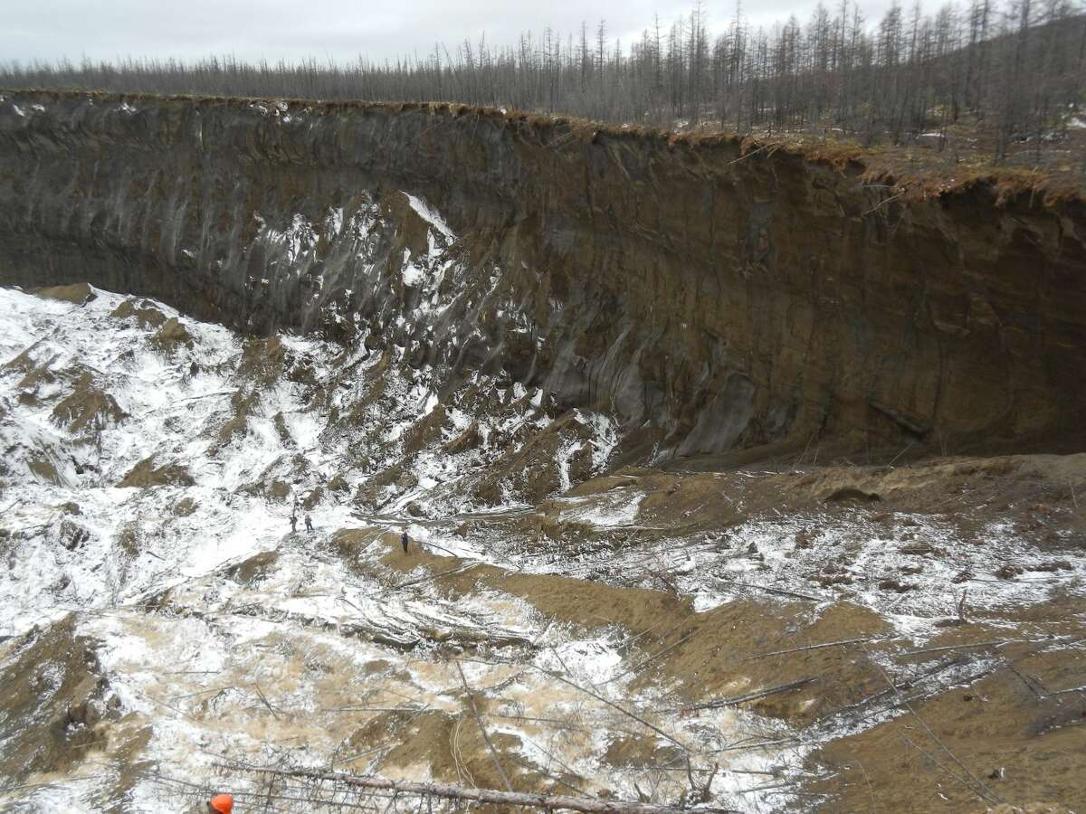 """From our story """"Exploding craters, gateway to underworld: What's not to like about global warming?""""The land in Alaska, Canada and Siberia is changing significantly along with a warmer climate because of the collapse of permafrost. It's not happening everywhere, yet, and the permafrost in many areas will last for millennia. But certainly some of it won't, and that's causing significant changes in the landscape.Take, for instance, the Batagaika crater or Batagaika mega-slump -- or, as the locals in Siberia have taken to calling it: """"The Gateway to the Underworld."""" There are also the exploding craters in the northwest Siberia, Russia, region (photos above). As reported June 7 by The Siberian Times: """"...respected scientist Dr Vladimir Epifanov, the sole leading expert to so far visit the site, said: 'There is verbal information that residents of nearby villages - at a distance of 70-100 km - heard a sound like an explosion, and one of them watched a clear glow in the sky. It was about one month after the Chelyabinsk meteorite.'"""" Photo: Slump headwall of the Batagaika crater in Siberia. People on slump floor."""