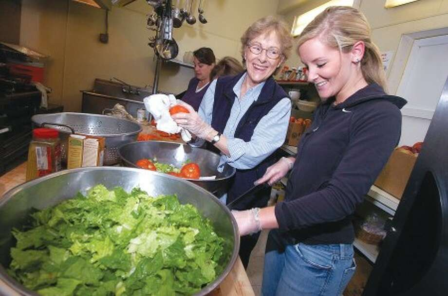 Photo/Alex von Kleydorff. L-r Ann Thompson from Darien and Katie Runckel from New Canaan prepare fresh salad for the lunch crowd at the Norwalk Open Door Shelter.
