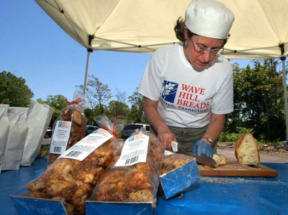 Photo/Alex von Kleydorff. Margaret Sapir, co owner of Wave Hill Breads, cuts up some samples of their rustic bread at the Westport Farmers Market.