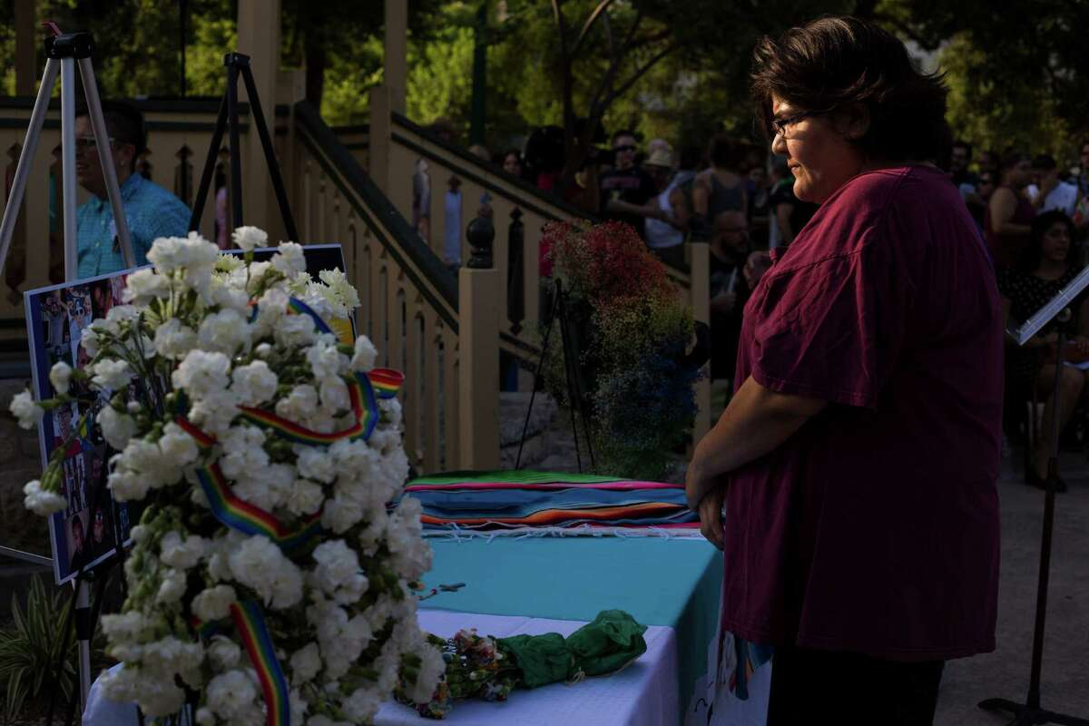 Carol Aguero, 44, of San Antonio quietly studies a memorial with photographs and flowers before the start of a vigil to honor the lives of the 49 victims killed in the recent mass shooting in Orlando, Fl., at Crockett Park in downtown San Antonio, on Thursday, June 16, 2016.