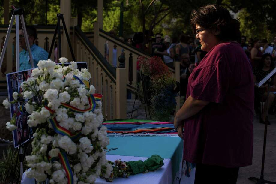 Carol Aguero, 44, of San Antonio quietly studies a memorial with photographs and flowers before the start of a vigil to honor the lives of the 49 victims killed in the recent mass shooting in Orlando, Fl., at Crockett Park in downtown San Antonio, on Thursday, June 16, 2016. Photo: BRITTANY GREESON, San Antonio Express-News / © 2015 San Antonio Express-News