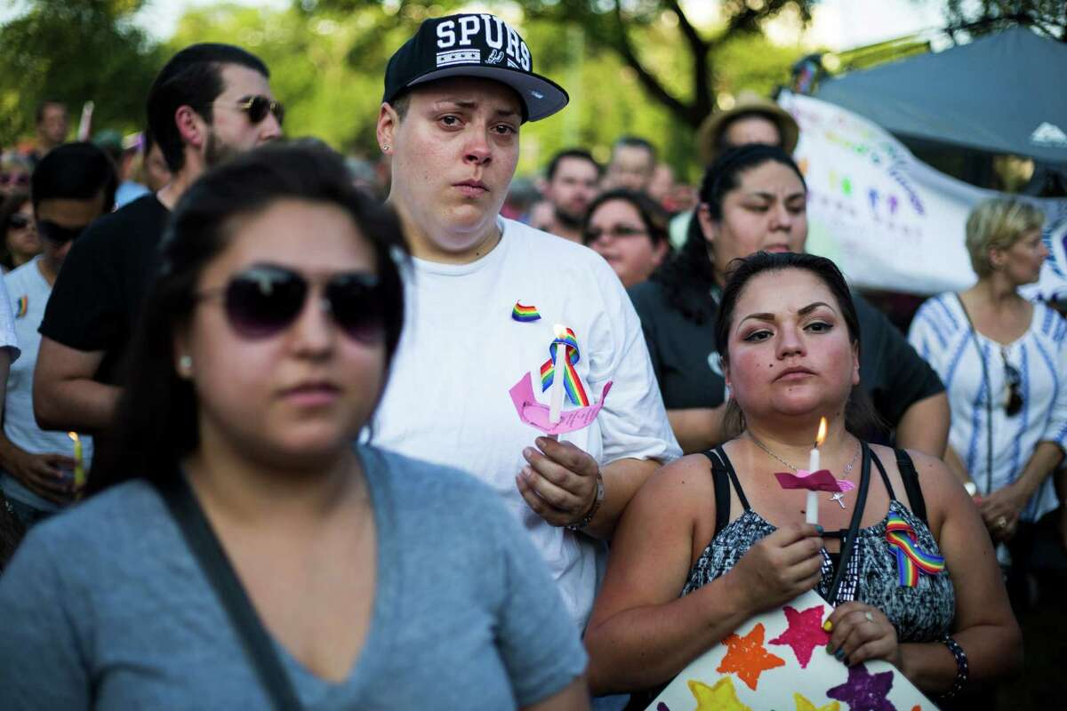 Amanda Glowka, 35, of San Antonio, sobs while holding candles alongside partner, April Hernandez, 29, during a vigil to honor the lives of the 49 victims killed in the recent mass shooting in Orlando, Fl., at Crockett Park in downtown San Antonio, on Thursday, June 16, 2016.