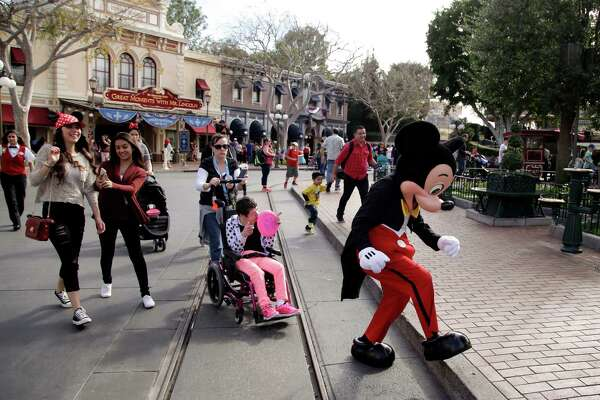 FILE - In this Jan. 22, 2015, file photo, visitors follow Mickey Mouse for photos at Disneyland in Anaheim, Calif. Disneyland, the original theme park, opened in 1955. Company founder Walt Disney oversaw its construction on a 65-hectare (160-acre) orange farm in what was then a semi-rural part of Orange County. The park's original four themed areas - Fantasyland, Frontierland, Adventureland and Tomorrowland - were later joined by Critter Country and New Orleans Square. A Star Wars-themed expansion is in the works. (AP Photo/Jae C. Hong, File)