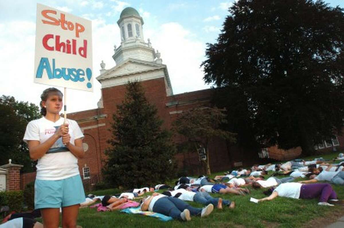 Brien McMahon student Gillian Minnerly stands with a Stop Child Abuse sign while other school members lay dead on the lawn of Norwalk City Hall Wednesday to raise awareness of children who die every day from child abuse/hour photo matthew vinci