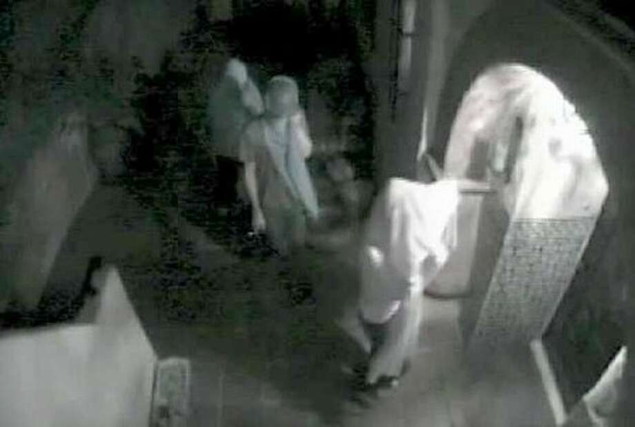A video still from a surveillance camera provided by the Los Angeles Police Department shows three suspects attempting to enter the Hollywood Hills home of actress Lindsay Lohan in August 2009 in Los Angeles. (AP Photo/Los Angeles Police Department)