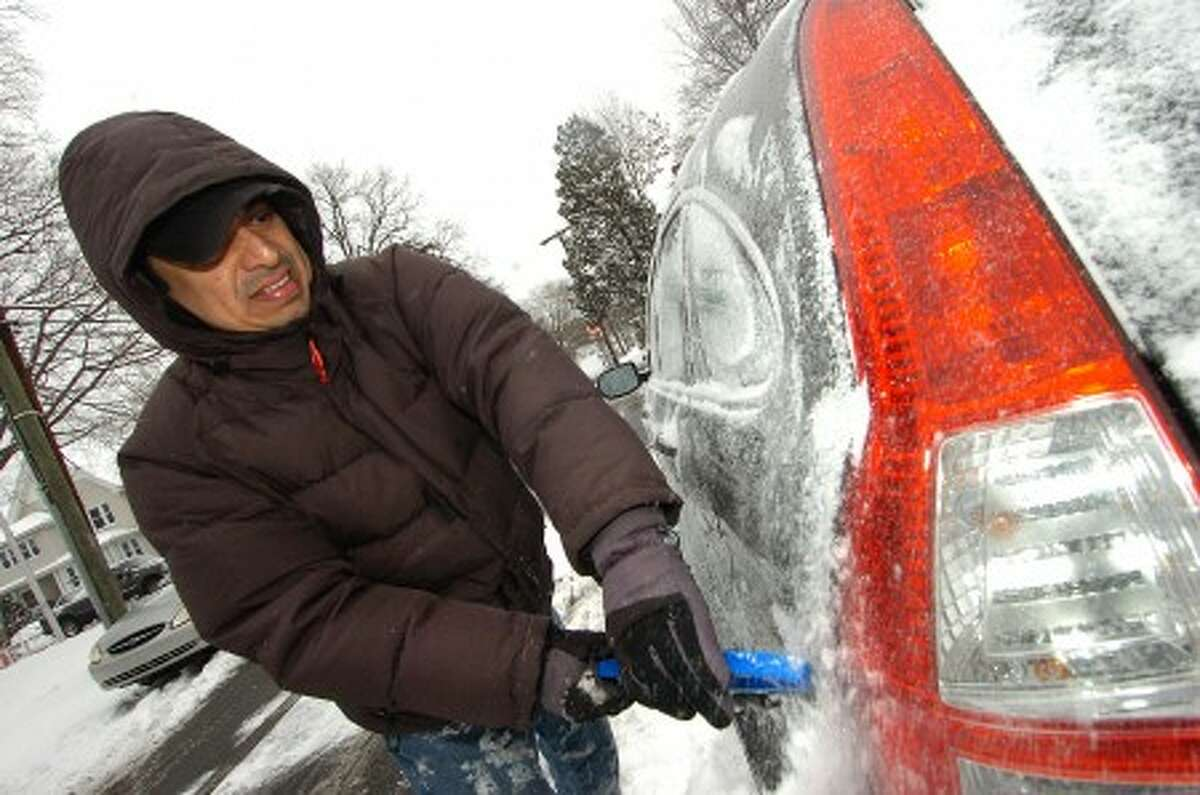 Photo/Alex von Kleydorff. jack Leiva clears the snow off his car on Monday morning in Stamford.