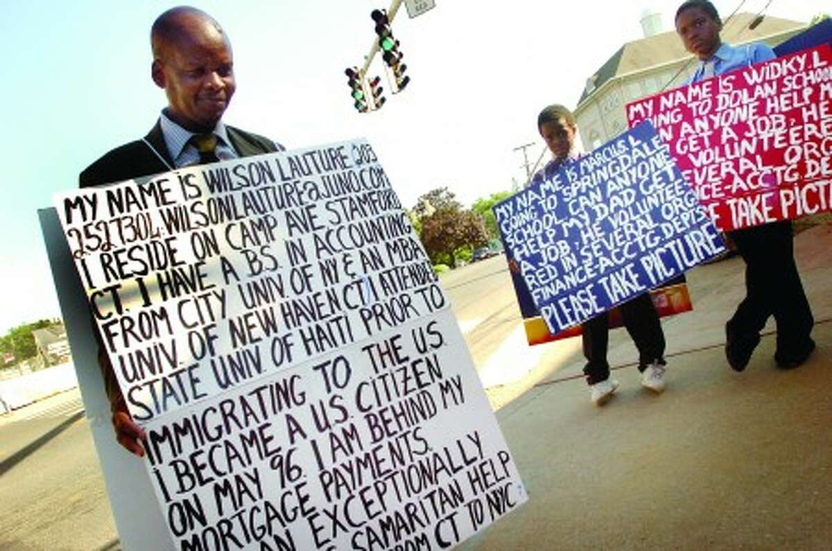 Wilson Lauture an accountant who immigrated to the U.S. from Haiti and is now laid off with his sons, Marcus 8 and Widky 12 stand on Cross street in Norwalk Friday wearing signs for help/hour photo matthew vinci