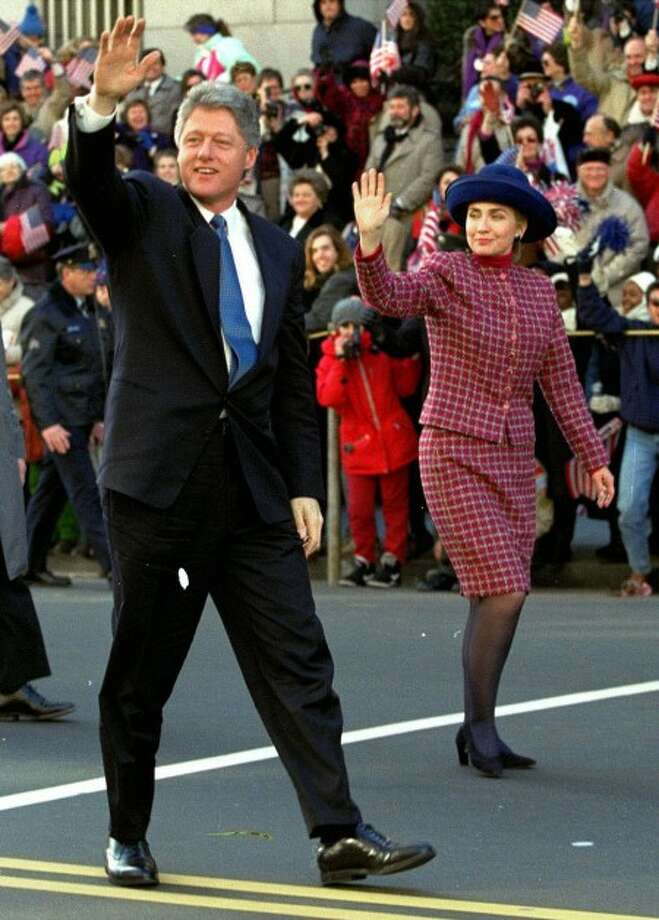 This Jan. 20, 1003 file photo shows President Clinton and his wife Hillary Rodham Clinton waving to the crowd as they walk down 15th Street in Washington during the presidential inaugural parade. When both Laura Bush and Hillary Clinton arrived at the White House, they both brought with them styles that suited their hometowns in Texas and Arkansas, but they wouldn''t have held up in any fashion capital. (AP Photo/Doug Mills, file)