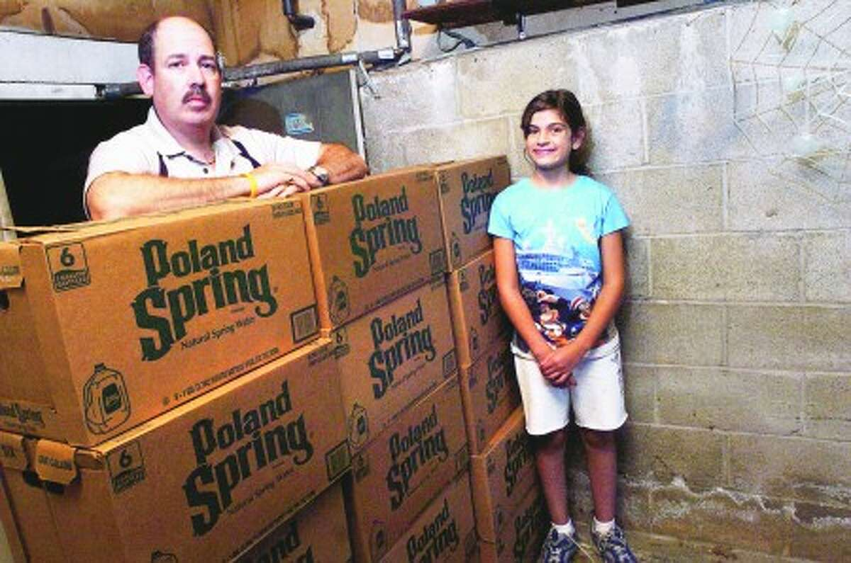 Homeowner Jason Alter with his 10 year old daughter Lindsay in his garage with a stack of bottled water that he has been using for the past 2 years. He uses no city water except for his shower. The bottled water is used cold and bolied hot for everyday use since a number of homes in the Scofieldtown area of Norh Stamford had their well water test positive for potentially deadly pesticides/photo matthew vinci