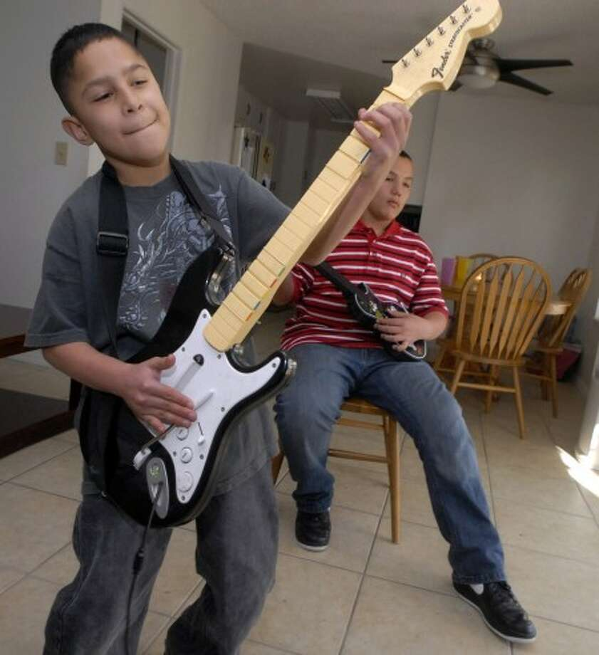 Gabe Sanchez, 12 plays lead guitar as one of his triplet brothers, Frank, play bass. MCT photo
