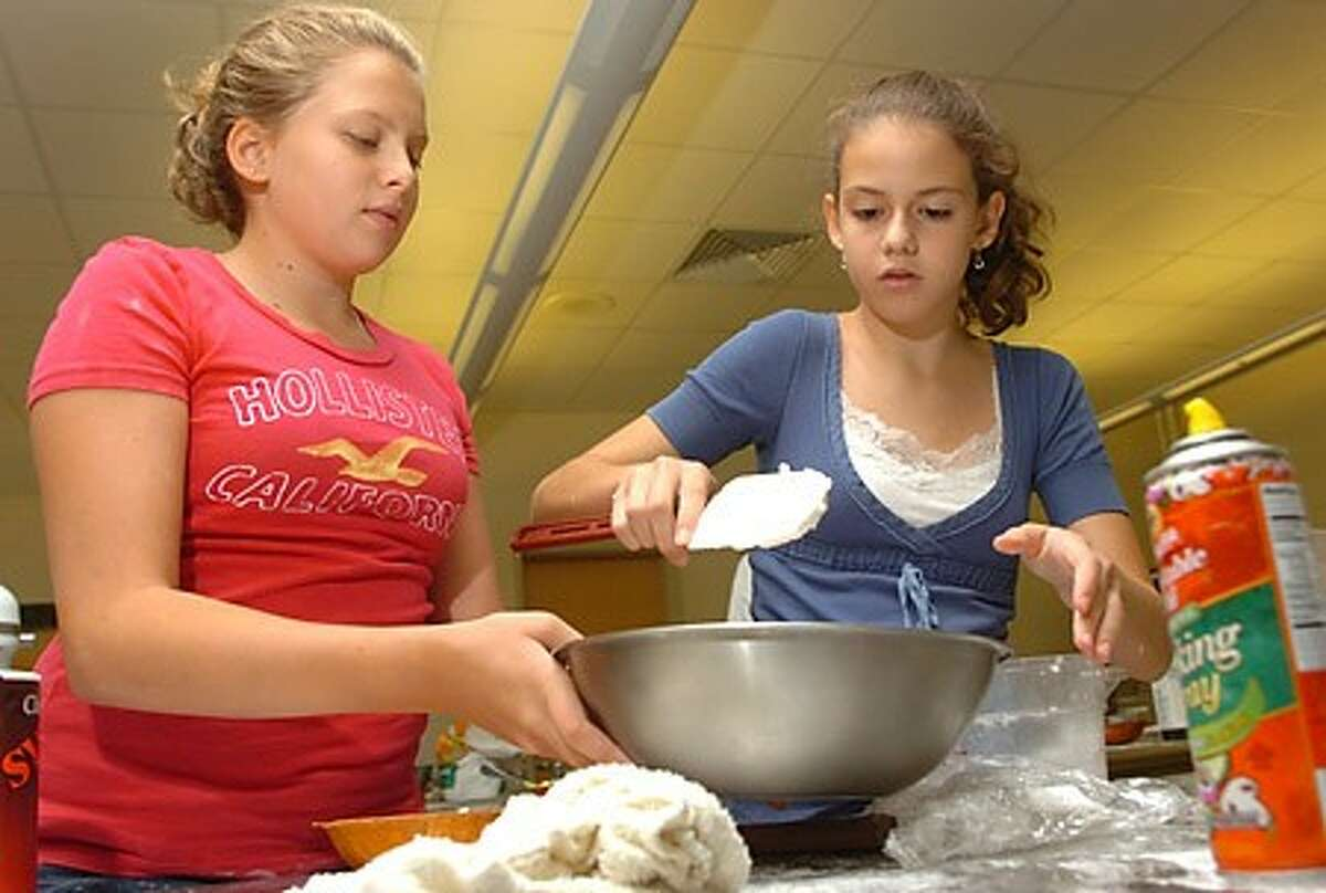 Middle Schoolers Sarah Henderson and Skyler Buswell mix up ingredients for their next project during the Norwalk Board of Education Summer Cooking Camp at Brien McMahon High School Thursday. Hour photo / Erik Trautmann