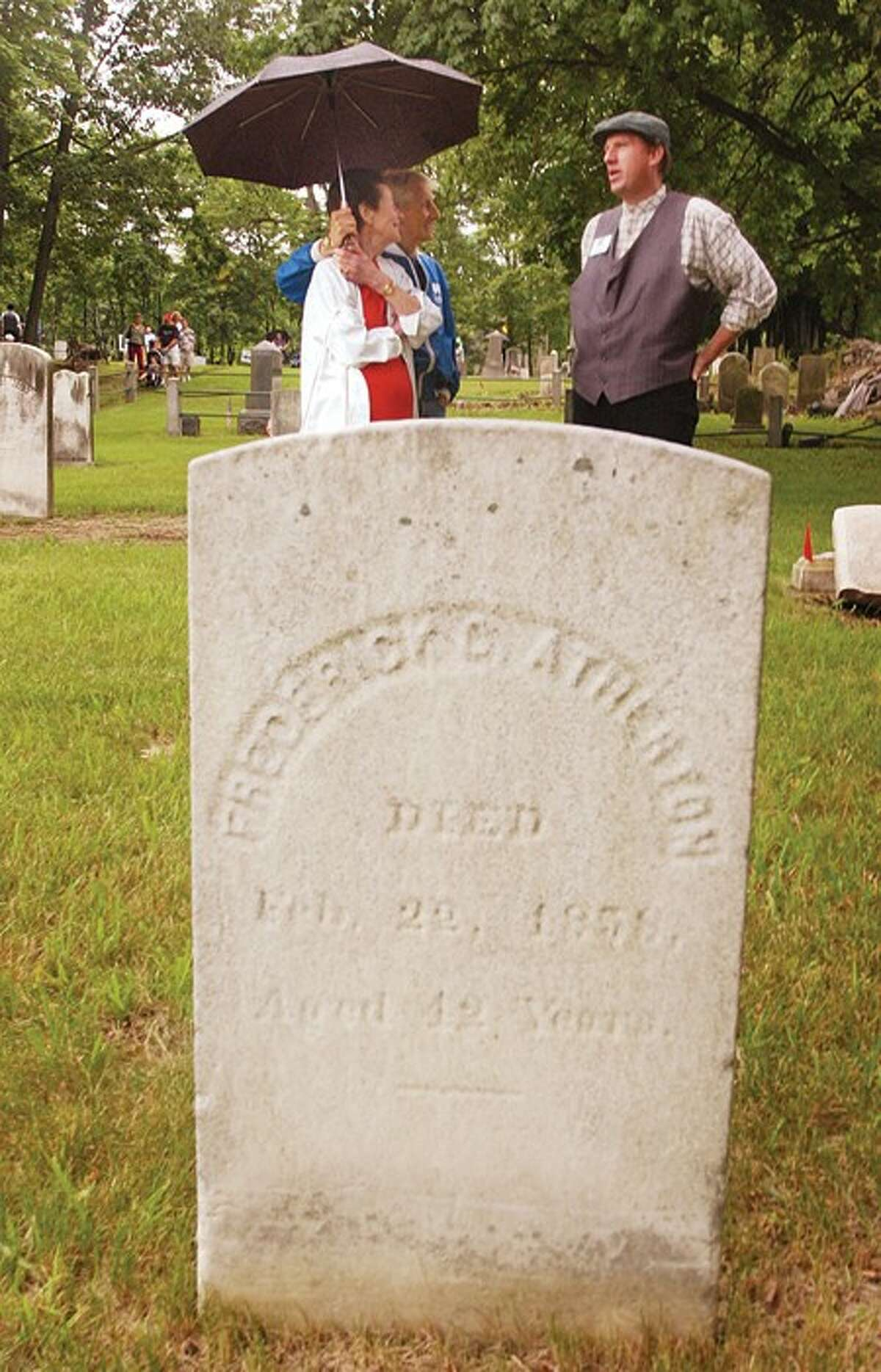 John Einstman portrays Federick Metz who died at the age of 19 when the ship, the Adelphi, sank while talking with Ed and Ann Devingo as part of the Pine Island Historical Cementary Tour during the Party in the Park event at Mathews Park Saturday. Hour photo / Erik Trautmann