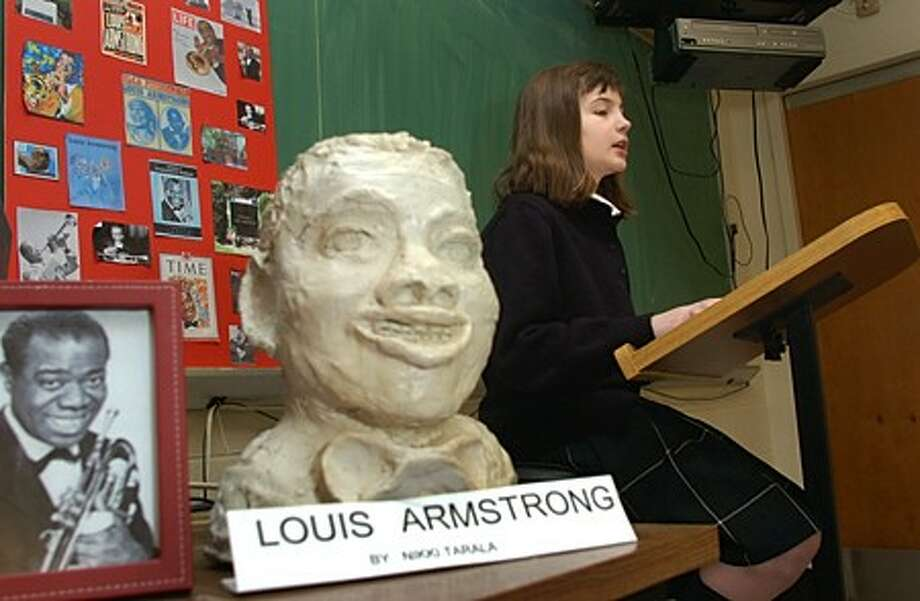 Nikki Torola, All Saints School 5th grader, gives her presentation on Louis Armstrong for her Black History Month project. The students made sculptures of the figures they studied to go along with their project that also included a presentation board and a DVD. Hour photo / Erik Trautmann