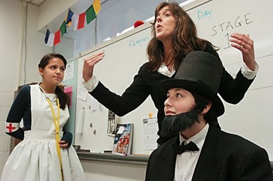 Roton Middle School 8th grade parent Jackie Liljegren, who has a drama backround, coaches students Melissa Rios and Eric Mordoff in improvisation as the students participate in Famous Americans Day at the school Friday. Hour photo / Erik Trautmann