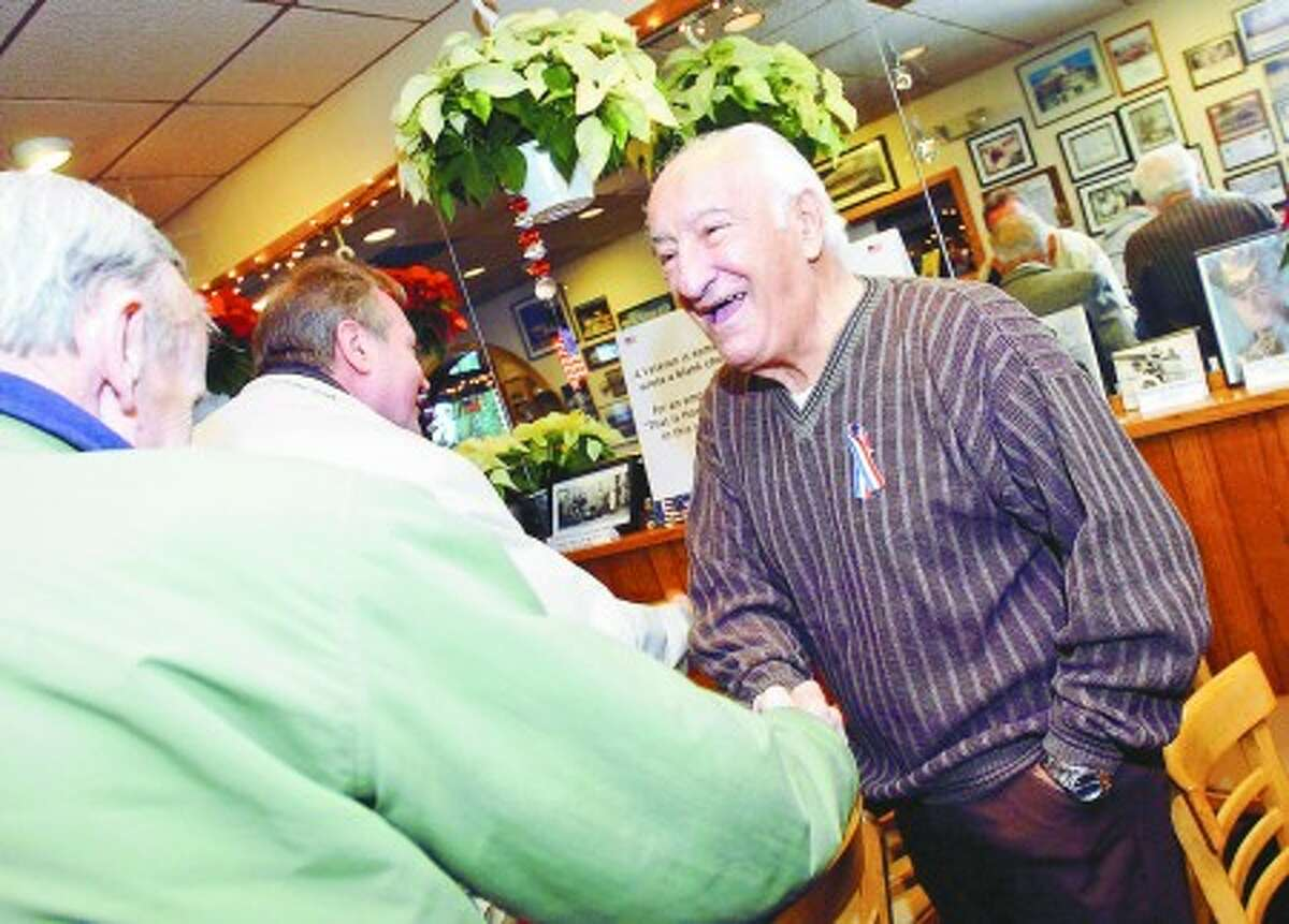 World War II veteran Babe Spinola shakes hands as he is introduced to Don Sexton, another World War II veteran, during a fundraiser at Partner''s Cafe in Norwalk Sunday afternoon. The fundraiser was held to bring veterans to Washington D.C. to see the memorials . Hour Photo / DANIELLE ROBINSON