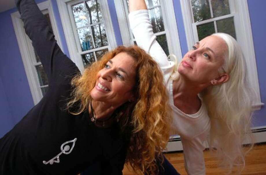 Photo/Alex von Kleydorff. l-R Harmony Yoga owner Carol Shwidock and certified Instructor Ann Russell in a Triangle pose in the Harmony Yoga studio