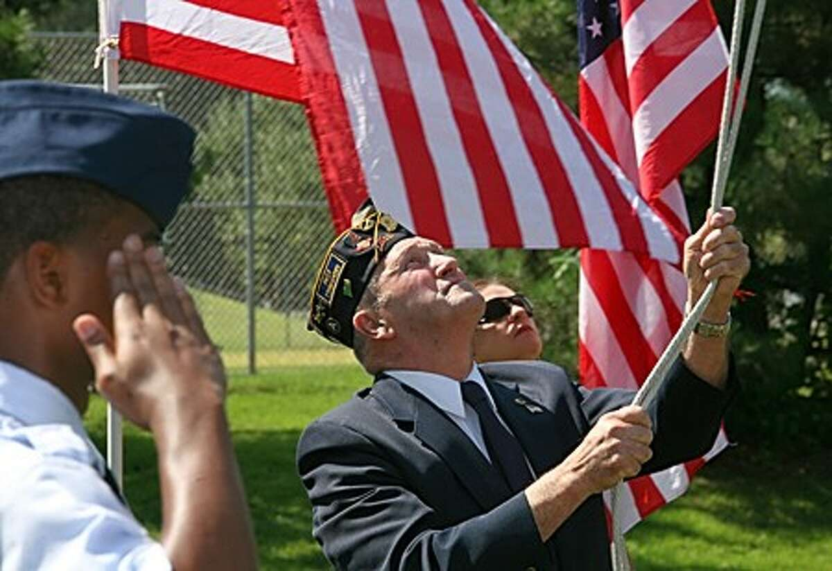 Bob Forbis brings a flag to half mast in honor of the American Legion''s Veteran of the Month, Paul D. Curioli, who fought in Vietnam and died at the World Trade Center on 9/11 during a service at the American Legion Hall in Norwalk Sunday morning. Hour Photo / Danielle Robinson