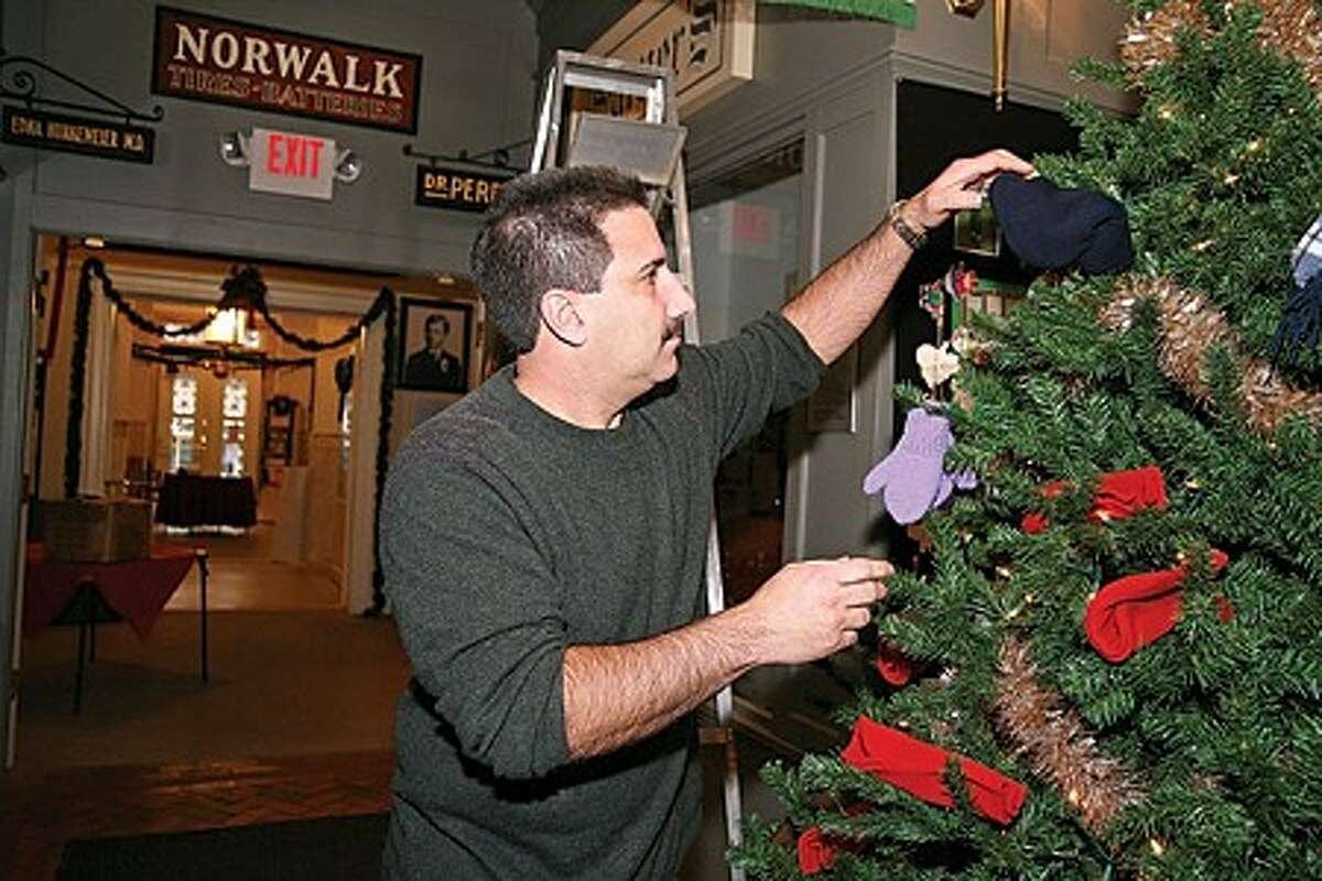 """Peter Bondi, Vice Chair of the Historical Committee, decorates The Giving Tree with a donated hat at the Norwalk Museum during the 1st Annual Holiday Stroll Sunday afternoon. The tree and its """"winter-wear"""" decorations will be donated to the Norwalk Emergency Shelter. Hour Photo / Danielle Robinson"""