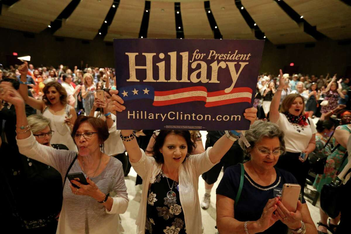 """Hillary Clinton delegate Angela Collins, of El Paso, (center) holds a """"Hillary for President"""" sign during the kickoff reception for the 2016 Texas Democratic Convention held Thursday June 16, 2016 at La Villita Assembly Hall."""
