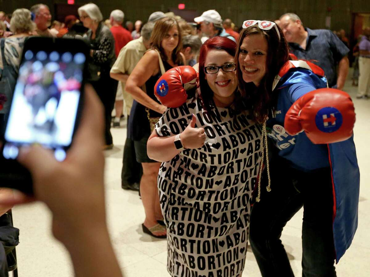 Hillary Clinton delegates Leah Payne, of Fort Worth, (left) and Kim Frederick, of Houston, pose for photos during the kickoff reception for the 2016 Texas Democratic Convention held Thursday June 16, 2016 at La Villita Assembly Hall.