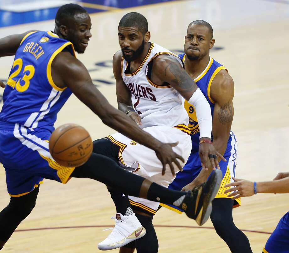 Cleveland Cavaliers guard Kyrie Irving (center) passes the ball between Golden State Warriors forward Draymond Green (left) and guard Andre Iguodala (right) during Game 3 of the NBA Finals in Cleveland, Ohio on June 8, 2016.  Photo: JAY LAPRETE, AFP/Getty Images