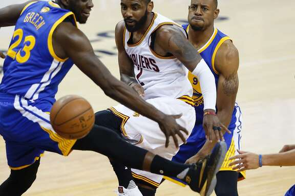 Cleveland Cavaliers guard Kyrie Irving (C) passes the ball between Golden State Warriors forward Draymond Green (L) and guard Andre Iguodala (R) during Game 3 of the NBA Finals in Cleveland, Ohio on June 8, 2016. / AFP PHOTO / Jay LaPreteJAY LAPRETE/AFP/Getty Images