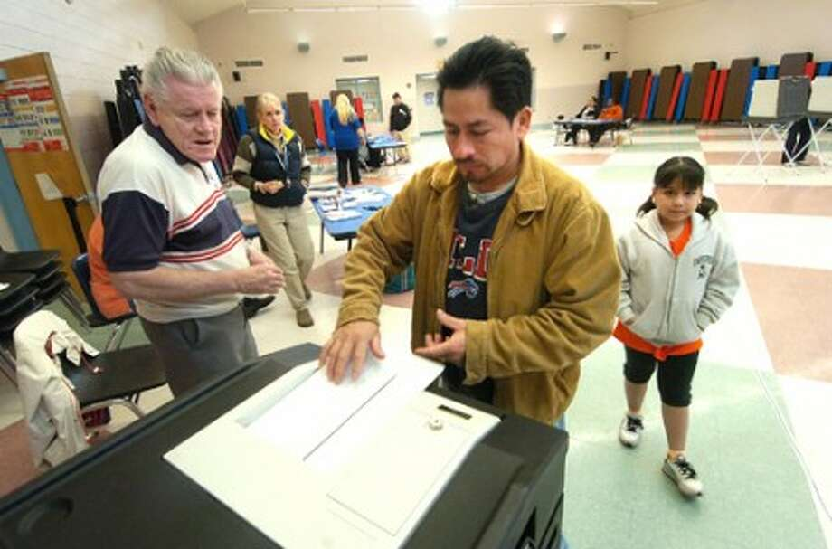 Photo/Alex von Kleydorff. Ballot Official Henry Hughes watches as Mario Lara casts his vote with his daughter 7yr old Skylark at Westover Magnet School in Stamford''s District 9 .