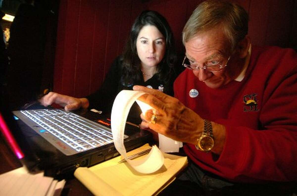 Photo/Alex von Kleydorff. Cristina Andreana and Frank Dell work with a flashlight on the tally of poll results at the Republican event in Stamford.
