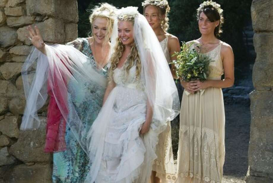 "Donna Sheridan (Meryl Streep, from left) celebrates her daughter Sophie''s (Amanda Seyfried) wedding with Sophie''s friends Lisa (Rachel McDowall) and Ali (Ashley Lilley) in the musical romantic comedy ""Mamma Mia!"" (Courtesy Peter Mountain/Universal Studios/MCT)"