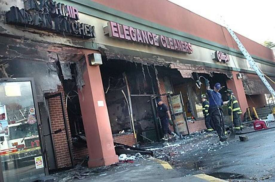 Norwalk Fire Department cleans out the area at Westport avenue where a number of stores were lost early on Monday in a fire/hour photo matthew vinci