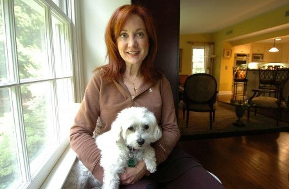 Photo/Alex von Kleydorff. Cancer survivor Sheryl Kraft with her Bicon Frise Chloe, in her Wilton home.