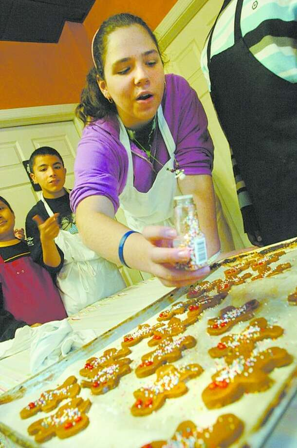 Olivia Shea 14, puts the finishing touches on gingerbread cookies at Stella''s Cafe & Bakery in Stamford on Monday morning whereThe schhol of Autismwere shown how to bake and the proceeds of the sale will go to the school/photo matthew vinci