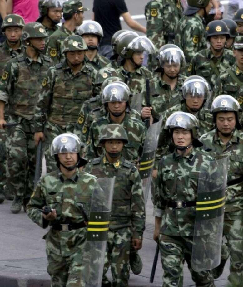 Chinese paramilitary police march by a square closed after riots in Urumqi, western China''s Xinjiang province, Monday, July 6 , 2009. (AP Photo/Ng Han Guan)