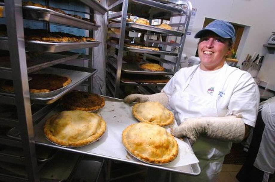 Photo/Alex von Kleydorff. Michele Albano takes some fresh from the oven Pear Raspberry and Apple pies to cool on the rack at Michele''s Pies in Norwalk.
