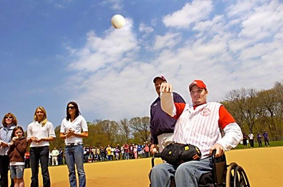 Former Cranbury Baseball coach and player, Anthony Angione, who was paralyzed in a motorcycle accident, throws out the first pitch at the league opening after a ceremony dedicating this season to Angione Saturday. Hour photo / Erik Trautmann
