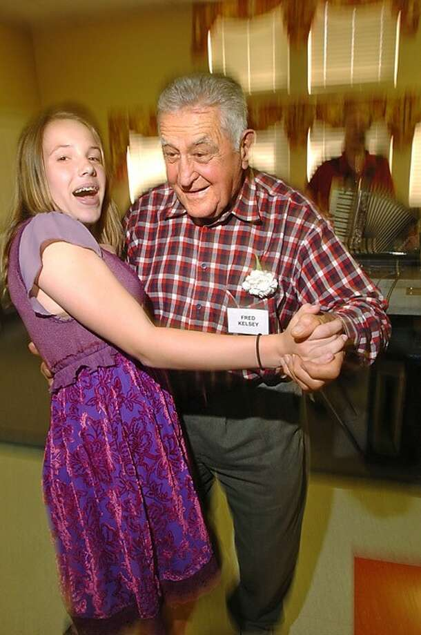 Fred Kelsey dances with Greens Farms Academy 7th grader during the school''s community service progam culmination Wednesday at Elderhouse. Hour photo / Erik Trautmann